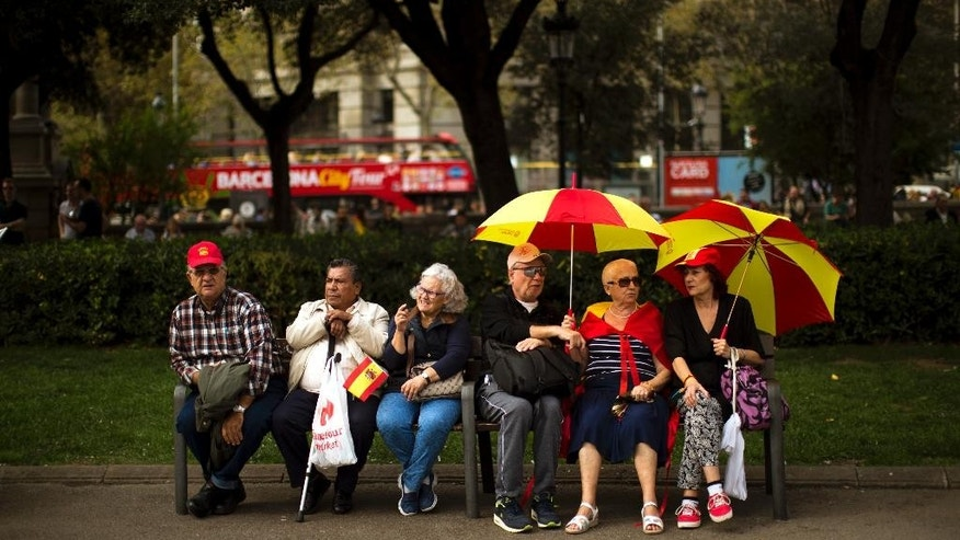 """People sit at a bench as they celebrate a holiday known as """"Dia de la Hispanidad"""" or Spain's Hispanic Day in Barcelona, Spain, Monday, Oct. 12, 2015. The Monday holiday commemorates Christopher Columbus' arrival in the New World and is also Spain's armed forces day. (AP Photo/Emilio Morenatti)"""
