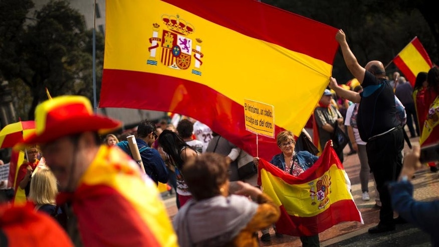 """People are photographed next to Spanish flags as they celebrate a holiday known as """"Dia de la Hispanidad"""" or Spain's Hispanic Day in Barcelona, Spain, Monday, Oct. 12, 2015. The Monday holiday commemorates Christopher Columbus' arrival in the New World and is also Spain's armed forces day. (AP Photo/Emilio Morenatti)"""