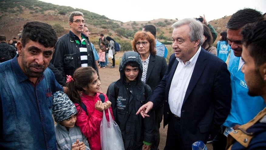 "United Nations High Commissioner for Refugees Antonio Guterres, third right, speaks with refugees and migrants who have just arrived, on the eastern Aegean island of Lesbos, Greece, Sunday Oct. 11, 2015. Greece's first ""hotspot,"" or migrant processing center, will open over the next 10 days, allowing migrants to be flown to other European Union countries, mostly of their preference, and have their asylum applications processed there, European Union officials say.  (AP Photo/Antonis Pasvantis)"