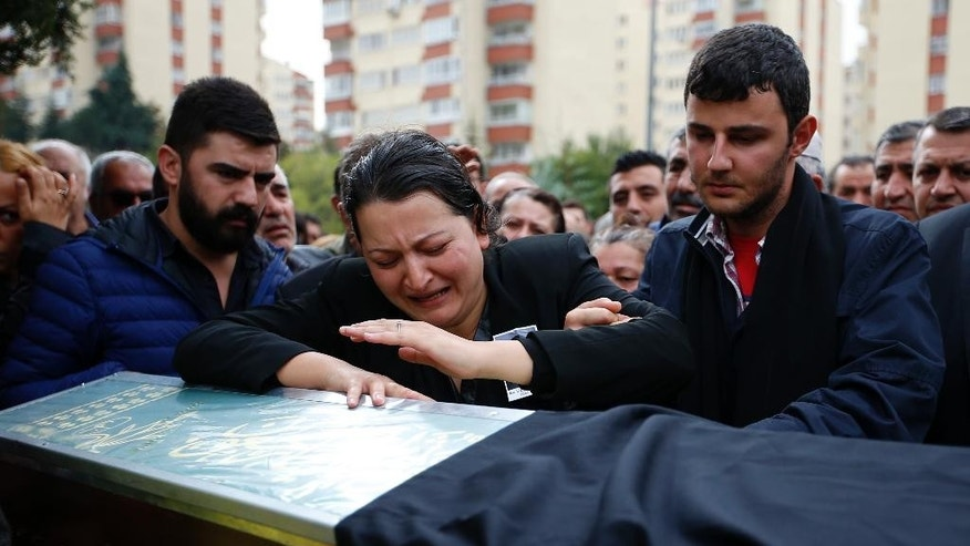 A relative cries over the coffin of Uygar Coskun, 32, killed in Saturday's bombing attacks, during his funeral, in Ankara, Turkey, Monday, Oct. 12, 2015. Authorities investigating the twin suicide bombings at a rally promoting peace with the Kurdish were focusing on the Islamic State group, comparing DNA samples of the suspected bombers with those obtained from families of extremists they suspect could have carried out the attacks, a newspaper close to the government reported on Monday. The government meanwhile, raised the death toll in Turkey's deadliest attack in years to 97 and said the victims included a Palestinian. (AP Photo/Emrah Gurel)