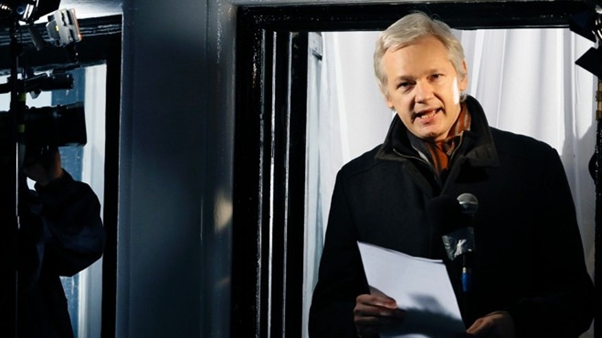 FILE - In this Thursday, Dec. 20, 2012, file photo, Julian Assange, founder of WikiLeaks speaks to the media and members of the public from a balcony at the Ecuadorian Embassy in London. British police have removed the officers standing watch over Julian Assange outside the Ecuadorean Embassy in London, but say they will still do their best to arrest the WikiLeaks founder who has been holed up there since June 2012. London's Metropolitan Police said in a statement Monday, Oct. 12, 2015, that Assange is still subject to arrest for failing to answer a rape charge in Sweden. (AP Photo/Kirsty Wigglesworth, File)