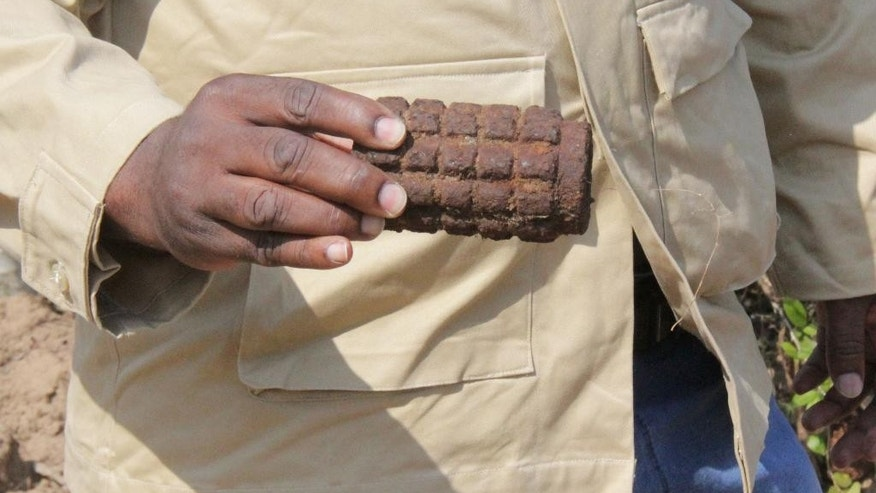 In this photo taken Wednesday Oct. 7, 2015 Lordes Zavale, an operations manager for APOPO,  Anti-Personnel Landmines Detection Product Development  a group helping to remove old ammunition from a former military depot in Mozambique, shows the remnants of an explosive that was found at the site. Accidental blasts at the former depot in the Malhazine neighborhood of Maputo killed more than 100 people in 2007. The Mozambican government plans to turn the area into a nature reserve with entertainment facilities after it is made safe for civilians.  (AP Photo/Ilec Vilanculo)