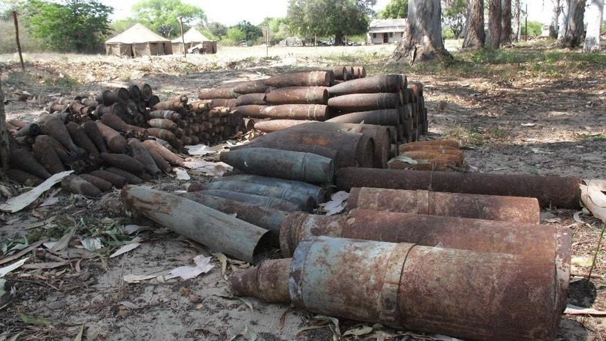 In this photo taken Wednesday Oct. 7, 2015 A pile of old rockets and other projectiles lies at a former military depot at Malhazine, a densely populated neighborhood in the Mozambican capital of Maputo, on Oct. 7, 2015.  Demining teams have been removing old ammunition from the site, where accidental explosions killed more than 100 people in surrounding areas in 2007. The Mozambican government plans to turn the former depot into a nature reserve after clearing it of dangerous military items (AP Photo/Ilec Vilanculo)