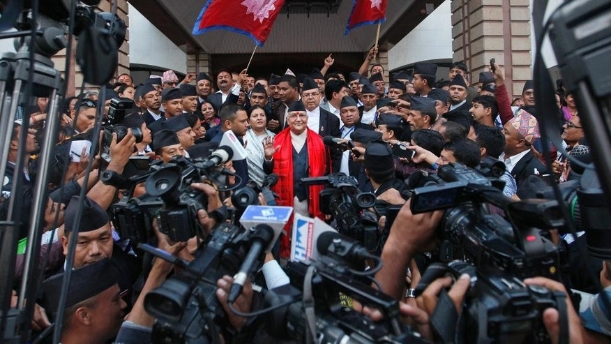 Nepal's newly-appointed prime minister Khadga Prasad Oli, center, is surrounded by journalists at the Constituent Assembly in Kathmandu, Nepal, Sunday, Oct. 11, 2015. Nepal's parliament elected Communist party leader Oli the new prime minister Sunday, thrusting him into the center of daunting challenges, from ethnic protests over the new constitution that has also upset vital neighbor India to rebuilding from April's devastating earthquake. (AP Photo/Niranjan Shrestha)