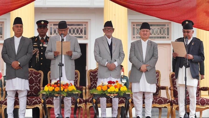 Nepal's President Ram Baran Yadav, second left, administers the oath of office to newly elected Prime Minister Khadga Prasad Oli, right, at the Presidential building in Kathmandu, Nepal, Monday, Oct. 12, 2015. Nepal's new prime minister took the oath of office Monday and appointed the leaders of groups that are protesting the new constitution as his deputies. (AP Photo/Niranjan Shrestha)