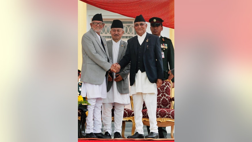 Nepal's newly elected prime minister Khadga Prasad Oli and former prime minister Sushil Koirala shake hands after Oli administered the oath of office to at the Presidential building in Kathmandu, Nepal, Monday, Oct. 12, 2015. Nepal's new prime minister took the oath of office Monday and appointed the leaders of groups that are protesting the new constitution as his deputies. (AP Photo/Niranjan Shrestha)