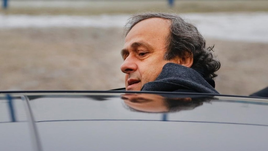 FILE - In this Jan. 19, 2015 file photo UEFA President Michel Platini gets into a car after a visit to the football arena in Minsk, Belarus. On Thursday, Oct. 8, 2015 file photo FIFA provisionally banned UEFA President Michel Platini for 90 days. (AP Photo/Sergei Grits)