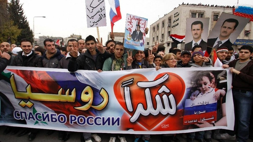 "FILE - In this Tuesday, Feb. 7, 2012 file photo, pro-Syrian government protesters hold a banner and a poster in Arabic that reads, ""Thanks Russia, Thanks China,"" as they cheer on a convoy believed to be transporting Russian Foreign Minister Sergey Lavrov in Damascus, Syria. The Arabic poster with Syrian President Bashar Assad's portrait reads, ""Bashar Assad, we love you and you will stay forever."" (AP Photo/Muzaffar Salman, File)"