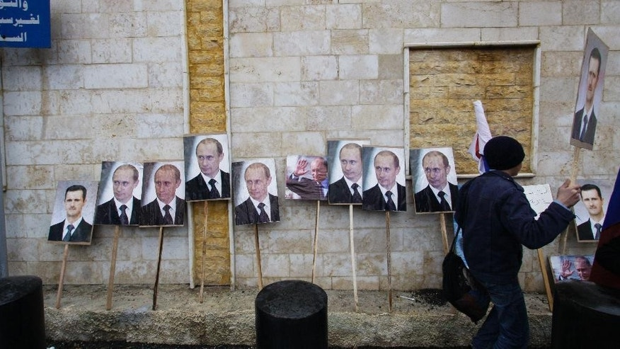 FILE - In this Sunday, March 4, 2013 file photo, photos of Syrian President Bashar Assad and Russian President Vladimir Putin are propped against a wall during a pro-Syrian government protest in front of the Russian Embassy in Damascus, Syria. Putin is winning plaudits from many Syrians and Iraqis, who see Russia's military intervention in Syria as a turning point after more than a year of largely ineffectual efforts by the U.S.–led coalition battling the Islamic State group. (AP Photo/Muzaffar Salman, File)