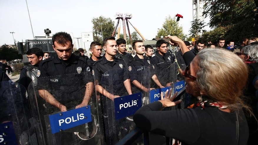 A protester throws carnations to Turkish police blocking the way to the site of Saturday's  explosions in Ankara, Turkey, Sunday, Oct. 11, 2015. Scuffles broke out as police prevented pro-Kurdish politicians and other mourners from laying carnations at the site of two suspected suicide bombings that killed 95 people and wounded hundreds in Turkey's deadliest attack in years. Police insisted investigators were still working at the site. (AP Photo/Emrah Gurel)