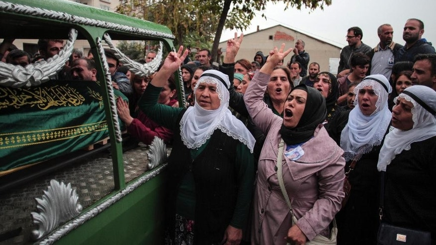 Mourners chant slogans as they escort a vehicle carrying the coffin of Sarigul Tuylu, 35, a mother of two that was killed in Saturday's bombing attacks in Ankara, Turkey, during her funeral in Istanbul, Sunday, Oct. 11, 2015. Turkey declared three days of mourning following Saturday's nearly simultaneous explosions that targeted a peace rally in Ankara to call for increased democracy and an end to the renewed fighting between the Turkish security forces and Kurdish rebels.  (AP Photo/Cagdas Erdogan)