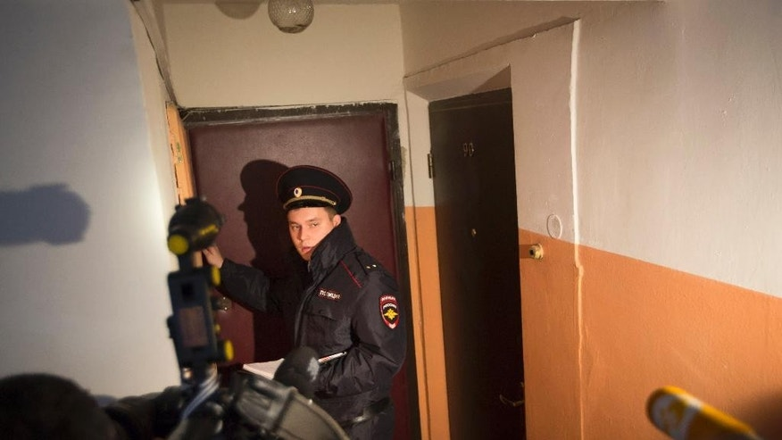 A Russian policeman speaks to the media in the building where homemade explosives were found in an apartment, in Moscow, Russia, Monday, Oct. 12, 2015. Russia's counterterrorism agency says it has raided a Moscow apartment and arrested a group of people who were preparing to carry out an attack in the capital. (AP Photo/Alexander Zemlianichenko)