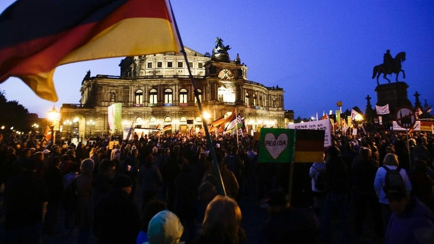 A protestor waves a German flag as he attends a demonstration of PEGIDA (Patriotic Europeans against the Islamization of the West) in front of the Semperoper, Dresden's famous opera house, in Dresden, Germany, Monday, Oct. 12, 2015. (AP Photo/Markus Schreiber)