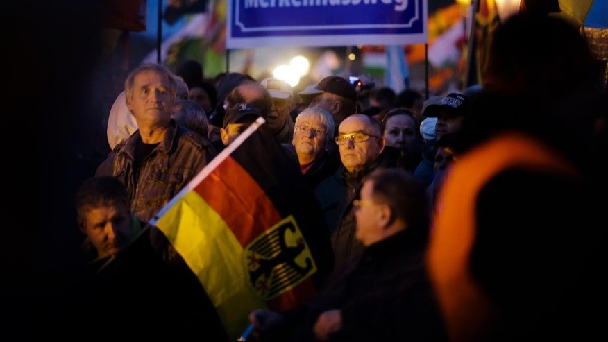 Protestors stand next to a poster reading 'Merkelmussweg' (Merkel must go) during a demonstration of PEGIDA (Patriotic Europeans against the Islamization of the West) in Dresden, Germany, Monday, Oct. 12, 2015. (AP Photo/Markus Schreiber)