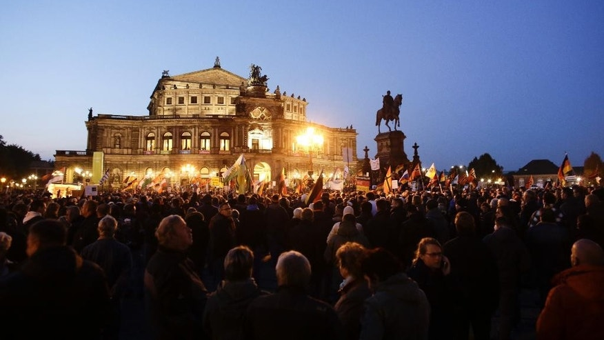 Protestors gather in front of the Semperoper, Dresden's famous opera house, during a demonstration of PEGIDA (Patriotic Europeans against the Islamization of the West) in Dresden, Germany, Monday, Oct. 12, 2015. (AP Photo/Markus Schreiber)