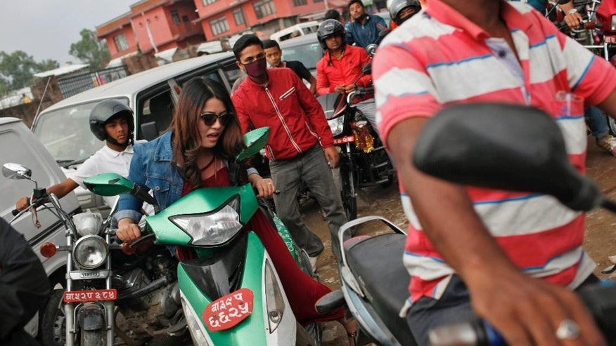 A Nepalese woman pushes her scooter forward as she waits for her turn to fill fuel at a gas station in Kathmandu, Nepal, Tuesday, Oct. 13, 2015. A China-Nepal border point that was damaged by April's devastating earthquake reopened Tuesday just as the small Himalayan nation struggles with supply shortages because of protests that have disrupted border points with India in the south. (AP Photo/Niranjan Shrestha)