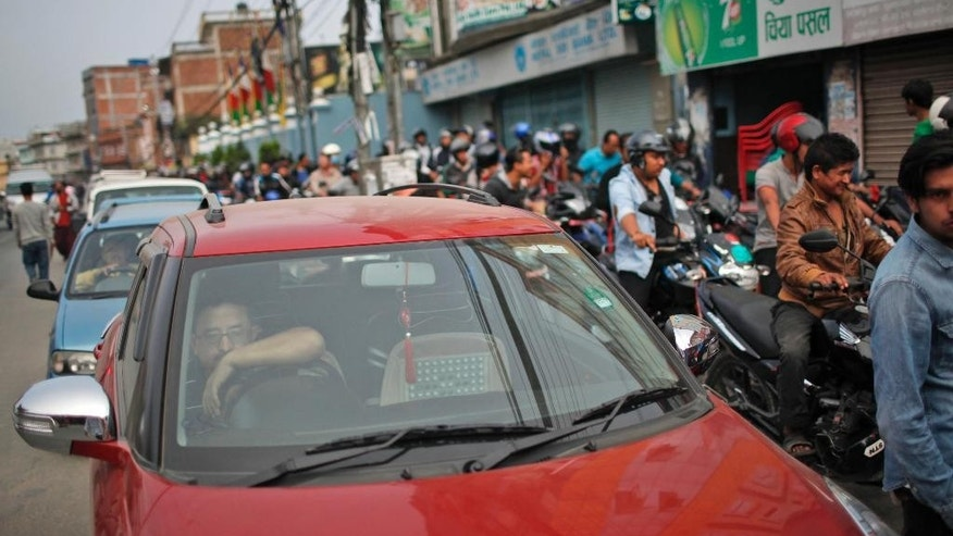 A Nepalese man sits inside his car as he waits for his turn to fill fuel at a gas station in Kathmandu, Nepal, Tuesday, Oct. 13, 2015. A China-Nepal border point that was damaged by April's devastating earthquake reopened Tuesday just as the small Himalayan nation struggles with supply shortages because of protests that have disrupted border points with India in the south. (AP Photo/Niranjan Shrestha)