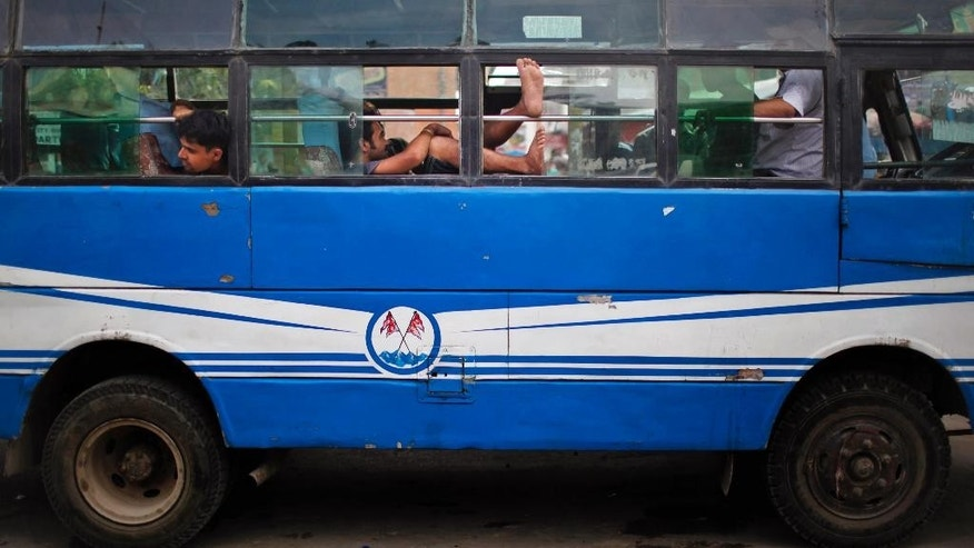 Nepalese bus drivers and conductors rest inside a bus after it ran out of fuel in Kathmandu, Nepal, Tuesday, Oct. 13, 2015. A China-Nepal border point that was damaged by April's devastating earthquake reopened Tuesday just as the small Himalayan nation struggles with supply shortages because of protests that have disrupted border points with India in the south. (AP Photo/Niranjan Shrestha)