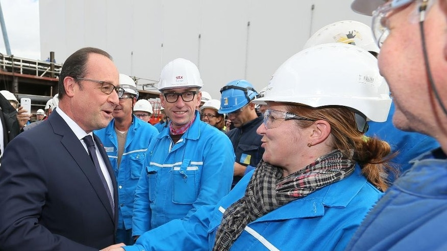 France's President Francois Hollande, left, shakes hands to a worker as he visits the shipyard of Saint-Nazaire, western France, Tuesday, Oct. 13, 2015. French president Francois Hollande says France is looking to sell new ships to Russia in the future despite the cancellation of the controversial deal for two Mistral-class warships earlier this year. The Mistral ships were instead sold to Egypt, a contract formally signed last week. (AP Photo/David Vincent, Pool)