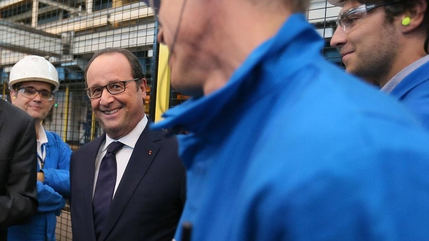 France's President Francois Hollande, left, listening to workers as he visits the shipyard of Saint-Nazaire, western France, Tuesday, Oct. 13, 2015. French president Francois Hollande says France is looking to sell new ships to Russia in the future despite the cancellation of the controversial deal for two Mistral-class warships earlier this year. The Mistral ships were instead sold to Egypt, a contract formally signed last week. (AP Photo/David Vincent, Pool)