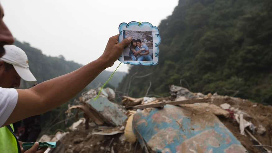 A resident holds up a photo of neighbors in Santa Catarina Pinula, about 10 miles of Guatemala City, Oct. 2, 2015.