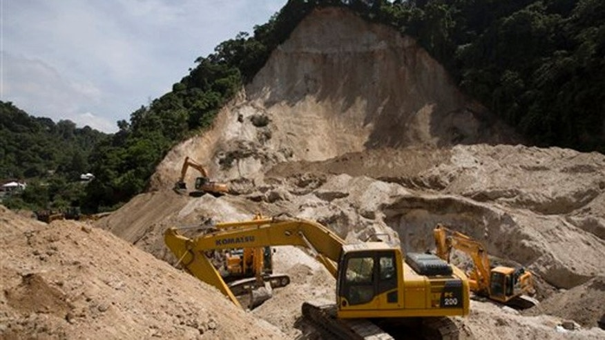 Oct. 9, 2015: Bulldozers sit at the site of a mudslide in Cambray, a neighborhood in the suburb of Santa Catarina Pinula, on the outskirts of Guatemala City.