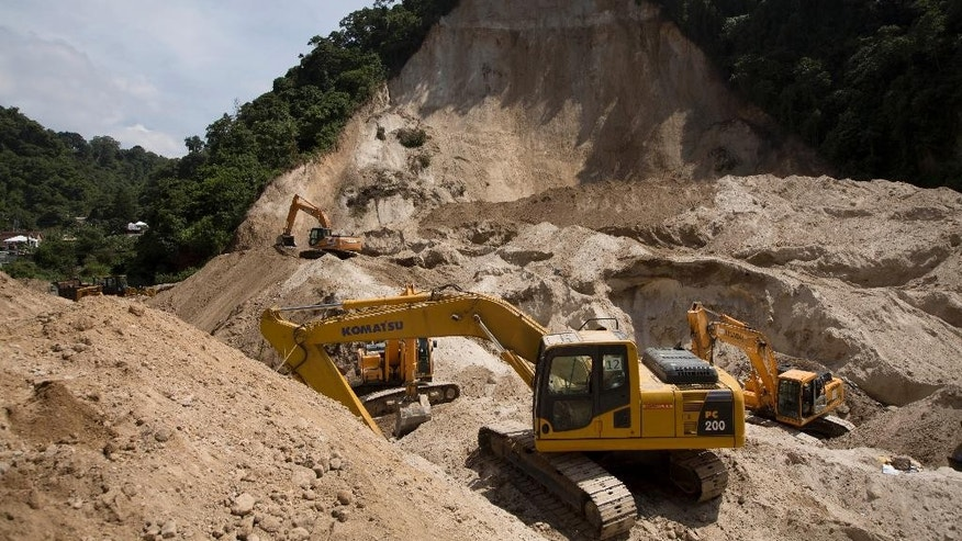 In this Oct. 9, 2015 photo, bulldozers sit at the site of a mudslide in Cambray, a neighborhood in the suburb of Santa Catarina Pinula, on the outskirts of Guatemala City. On Tuesday, Oct. 13, 2015, authorities called off the search for victims buried under a massive landslide that killed at least 280 people near the Central American nation's capital. (AP Photo/Moises Castillo)