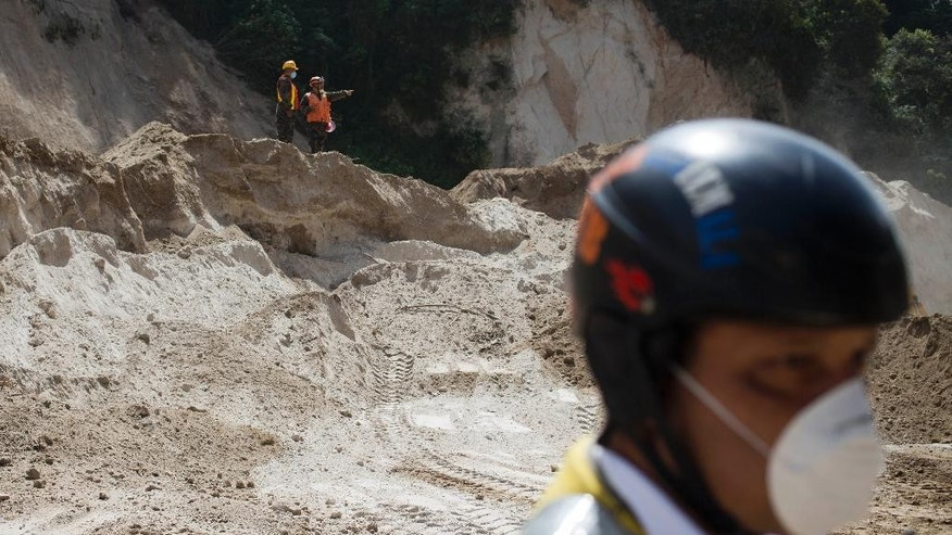 Rescue workers leave the site of a mudslide on the last day of searching for victims in Cambray, a neighborhood in the suburb of Santa Catarina Pinula on the outskirts of Guatemala City, Tuesday, Oct. 13, 2015. Authorities are calling off the search for victims buried under the massive landslide that killed at least 280 people and left 70 missing. The National Disaster Reduction Commission said it will be up to the local government to decide if the disaster area is declared a gravesite. (AP Photo/Moises Castillo)