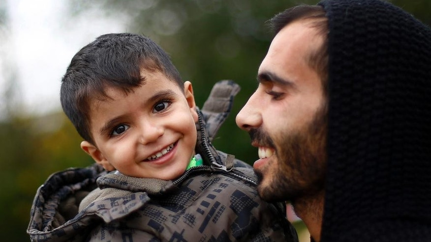 A man carries a young boy after arriving at the border between Austria and Germany in Salzburg, Austria, Tuesday, Oct. 13, 2015. (AP Photo/Matthias Schrader)