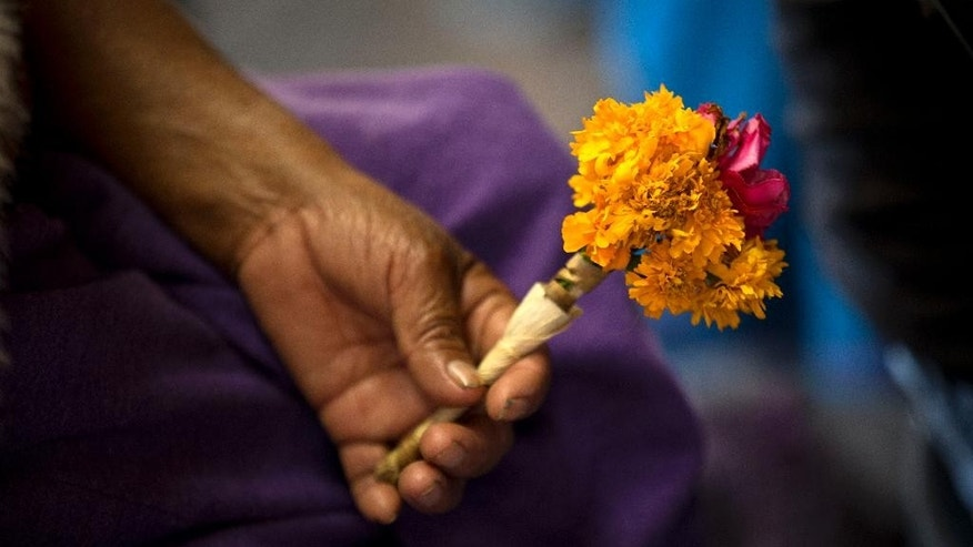 A woman holds flowers as she listens to a Mass celebrated in the indigenous language of Nahuatl, at the Basilica of Guadalupe in Mexico City, Tuesday, Oct. 13, 2015. Some parishioners wore crowns of marigolds for Basilica's first ever mass in Nahuatl. (AP Photo/Rebecca Blackwell)