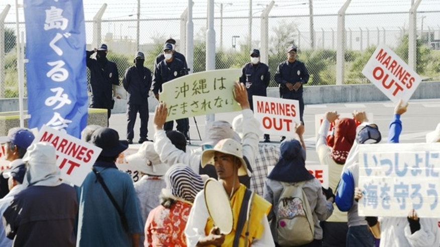 Oct. 13, 2015: Locals protest outside the fence of Camp Schwab, an American base near a planned relocation site of a U.S. air base, in Nago, Okinawa, southern Japan. (Koji Harada/Kyodo News via AP)