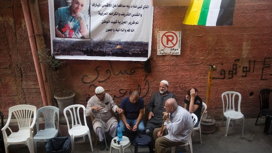 "In this Monday, Oct. 12, 2015 photo, Palestinians sit under a poster showing Mohammed Ali, 19, in Shafat refugee camp in Jerusalem. Ali was killed after he stabbed an Israeli policeman on Oct. 10 near Old City's Damascus Gate. The Arabic on the poster reads:  ""The one who has responded to God's call defending the sacred Al-Aqsa and Jerusalem and Arab dignity. Sleep well, martyr of the homeland. We are from God and we are turning back to him."" (AP Photo/Dusan Vranic)"