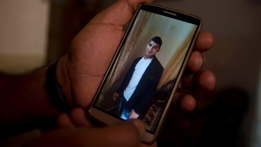 In this Monday, Oct. 12, 2015 photo, Ibrahim Abu Khalifeh shows a photo of his son Subhi, 19, at his home in Shuafat refugee camp in Jerusalem. Subhi stabbed and seriously wounded an Israeli man near Jerusalem's light rail before he was arrested. He grew up in the camp, one of the poorest areas of east Jerusalem, the part of the city captured by Israel in 1967 and home to its Arab neighborhoods. (AP Photo/Dusan Vranic)