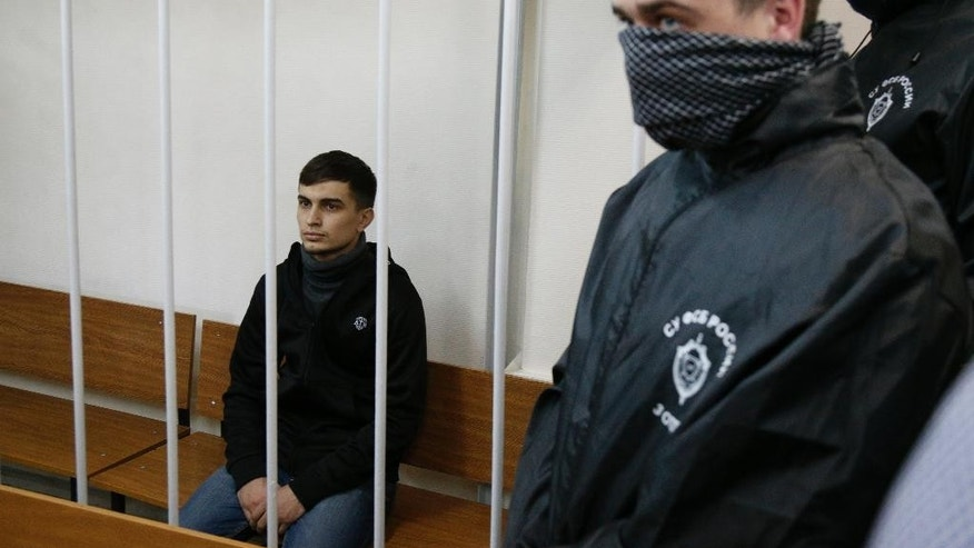 Aslan Baisultanov, a man suspected of plotting a terrorist attack in Moscow, sits in a defendants' cage as two intelligence officials with their faces covered, stand in a court room in Moscow, Russia, Tuesday, Oct. 13, 2015. Security officials said the suspects arrested Sunday were trained by the Islamic State group and had planned a terror attack on the Moscow public transport system. (AP Photo/Alexander Zemlianichenko)
