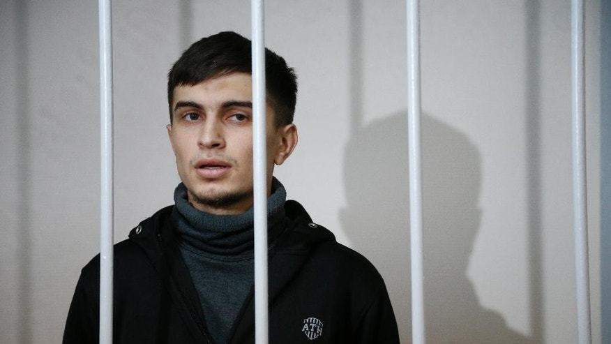 Aslan Baisultanov, a man suspected of plotting a terrorist attack in Moscow, sits in a defendants' cage in a court room in Moscow, Russia, Tuesday, Oct. 13, 2015. Security officials said the suspects arrested Sunday were trained by the Islamic State group and had planned a terror attack on the Moscow public transport system. (AP Photo/Alexander Zemlianichenko)