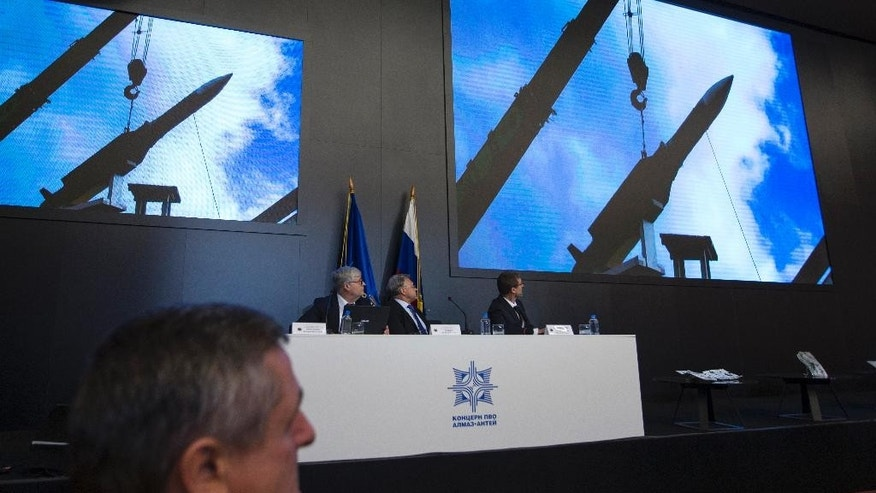 Almaz-Antei director Yan Novikov, center, looks at the screen during a news conference in Moscow, Russia, Tuesday, Oct. 13, 2015. Almaz-Antei air defense consortium, the builder of Buk missiles, presented its vision of the MH-17 air crash based on a new modeling of the disaster they recently conducted. (AP Photo/Pavel Golovkin)