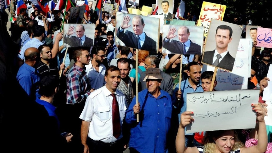 "CORRECTS PUTIN's TITLE - This photo released by the Syrian official news agency SANA, shows Syrians holding photos of Syrian President Bashar Assad and Russian President Vladimir Putin, during a rally to thank Moscow for its intervention in Syria, in front of the Russian embassy in Damascus, Syria, Tuesday, Oct. 13, 2015. Insurgents fired two shells at the Russian embassy in the Syrian capital on Tuesday as hundreds of pro-government supporters gathered outside the compound to thank Moscow for its intervention in Syria. The placard at right with Arabic reads, ""yes to Russian-Syrian cooperation."" (SANA via AP)"