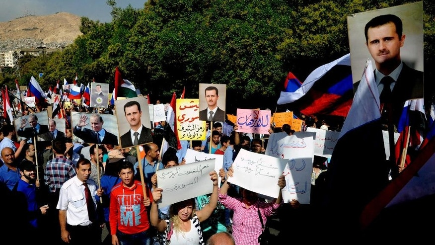 "CORRECTS PUTIN's TITLE  - This photo released by the Syrian official news agency SANA shows, Syrians holding photos of Syrian President Bashar Assad and Russian President Vladimir Putin, during a protest to thank Moscow for its intervention in Syria, in front of the Russian embassy in Damascus, Syria, Tuesday, Oct. 13, 2015. Insurgents fired two shells at the Russian embassy in the Syrian capital on Tuesday as hundreds of pro-government supporters gathered outside the compound to thank Moscow for its intervention in Syria. The placards in Arabic read, ""yes to Russian-Syrian cooperation,"" center left,  and ""thank you Russia, thank you Russia,"" center right. (SANA via AP)"