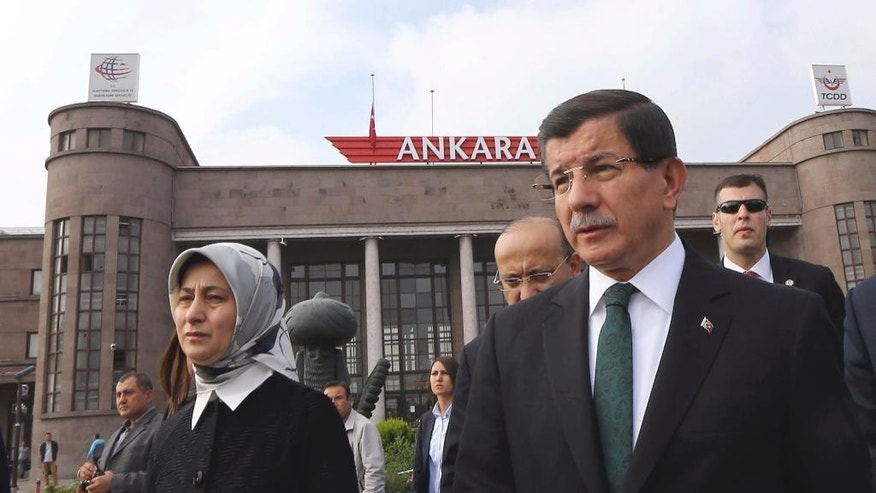 Turkish Prime Minister Ahmet Davutoglu and his wife Sare Davutoglu arrive to offer carnations at the site of an explosion in Ankara, Turkey, Tuesday, Oct. 13, 2015. Authorities in Istanbul banned a protest rally and march by the same trade union and civic society groups who lost friends and colleagues in Turkey's bloodiest terror attack. Dogan news agency video footage on Tuesday showed police pushing back dozens of demonstrators trying to reach the rally to commemorate the 97 victims of the twin suicide bombings. Some demonstrators were detained. (Hakan Goktepe/Prime Ministry Press Service via AP, Pool)