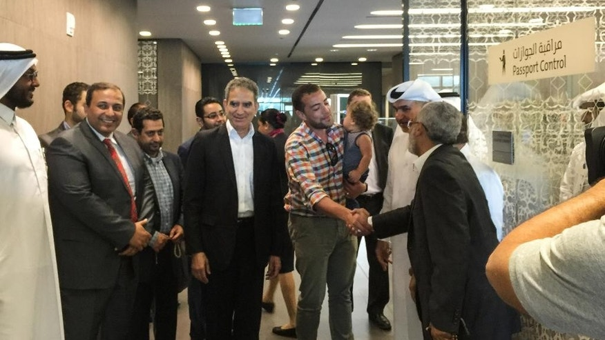 Egyptian Al-Jazeera English journalist Baher Mohammed, center, is welcomed by his colleagues upon his arrival to Doha, Qatar, Wednesday, Oct. 14, 2015. Baher and his Canadian colleague Mohamed Fahmy were among a group of 100 people pardoned by Egyptian President Abdel-Fattah el-Sissi on the eve of the major Muslim holiday of Eid al-Adha. (AP Photo)