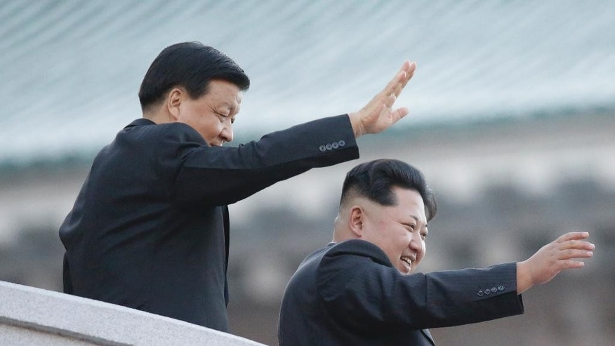 FILE - In this Saturday, Oct. 10, 2015 file photo, North Korean leader Kim Jong Un, right, waves his hand with Chinese official Liu Yunshan during a military parade to mark the 70th anniversary of the North's ruling party and trumpet his third-generation leadership in Pyongyang, North Korea. The two men raised their clasped hands above their heads like a pair of victorious athletes, as international media and tens of thousands of North Koreans looked on. The gesture by the North Korean leader and a top Chinese official during a high-profile celebration in Pyongyang seemed designed to scotch appearances that their countries have been drifting apart. (AP Photo/Wong Maye-E, File)