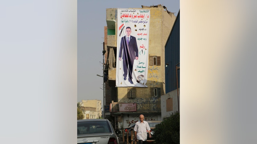 "An Egyptian walks in front of a banner of parliamentary candidate ""Ehab Mabrouk"", in Giza, near Cairo, Egypt, Wednesday, Oct. 14, 2015. Egypt's long-awaited parliamentary elections will start on Oct. 18-19, a hoped-for step toward democracy amid a harsh crackdown on dissent. The second stage of the staggered vote will take place on Nov. 22-23. Final results will be announced in early December. (AP Photo/Amr Nabil)"