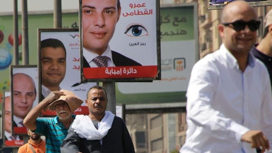 Egyptians walk in front of posters of parliamentary candidates, in Giza, near Cairo, Egypt, Wednesday, Oct. 14, 2015. Egypt's long-awaited parliamentary elections will start on Oct. 18-19, a hoped-for step toward democracy amid a harsh crackdown on dissent. The second stage of the staggered vote will take place on Nov. 22-23. Final results will be announced in early December. (AP Photo/Amr Nabil)