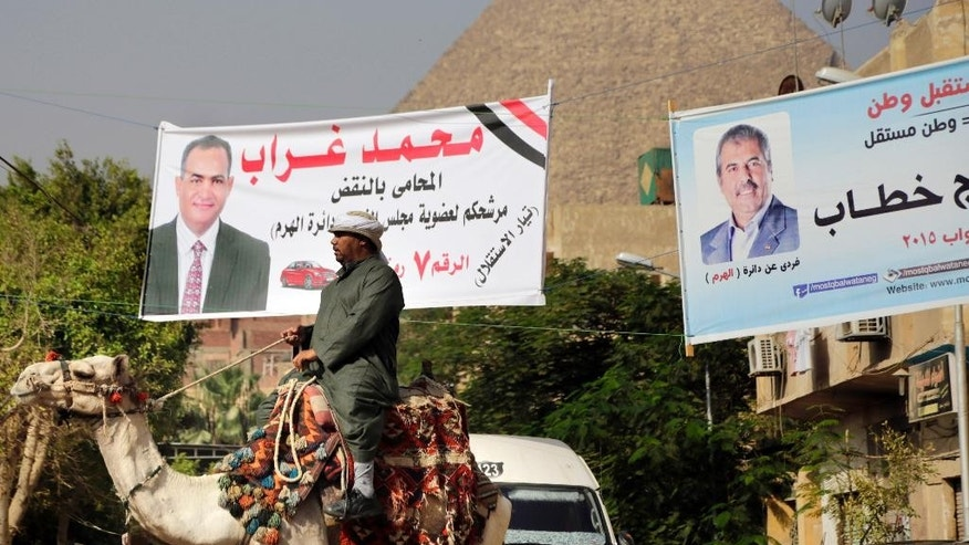 "An Egyptian tourist guide rides his camel in front of banners with pictures of parliamentary candidates, and Arabic that reads, ""Mohammed Ghorab"", left, and ""Farag Khatab"", right, in front of the historical site of the Giza Pyramids, near Cairo, Egypt, Wednesday, Oct. 14, 2015. Egypt's long-awaited parliamentary elections will start on Oct. 18-19, a hoped-for step toward democracy amid a harsh crackdown on dissent. The second stage of the staggered vote will take place on Nov. 22-23. Final results will be announced in early December. (AP Photo/Amr Nabil)"