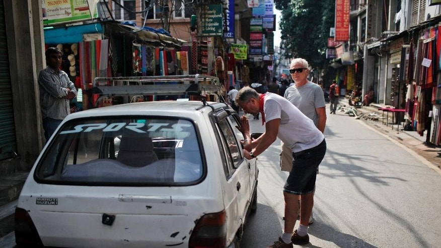 In this Tuesday, Oct. 13, 2015 photo, a tourist bargains the fare with a cab driver in Thamel, the tourist hub in Kathmandu, Nepal. Just when Nepal was recovering from the devastating earthquake that killed thousands, flattened hundreds of thousands of houses and chased away foreign tourists, protests by ethnic groups and severe fuel shortages are again keeping visitors away from the nation known for highest peaks in the world. (AP Photo/Niranjan Shrestha)