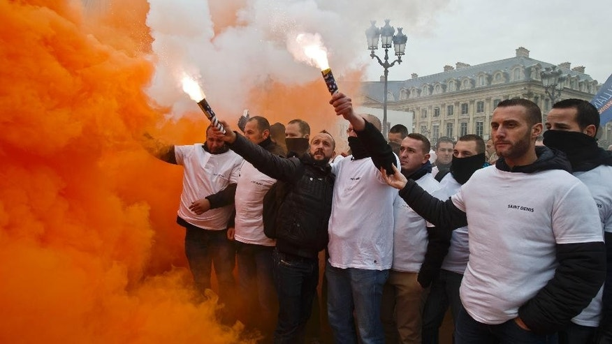 French police officers holding flares gathering next to the French justice ministry to demand better working conditions in Paris, Wednesday, Oct. 14, 2015. Police across France protest what they say are increasingly unsafe working conditions, pointing to the example of an officer critically wounded by a convict who never returned from a prison furlough. (AP Photo/Michel Euler)