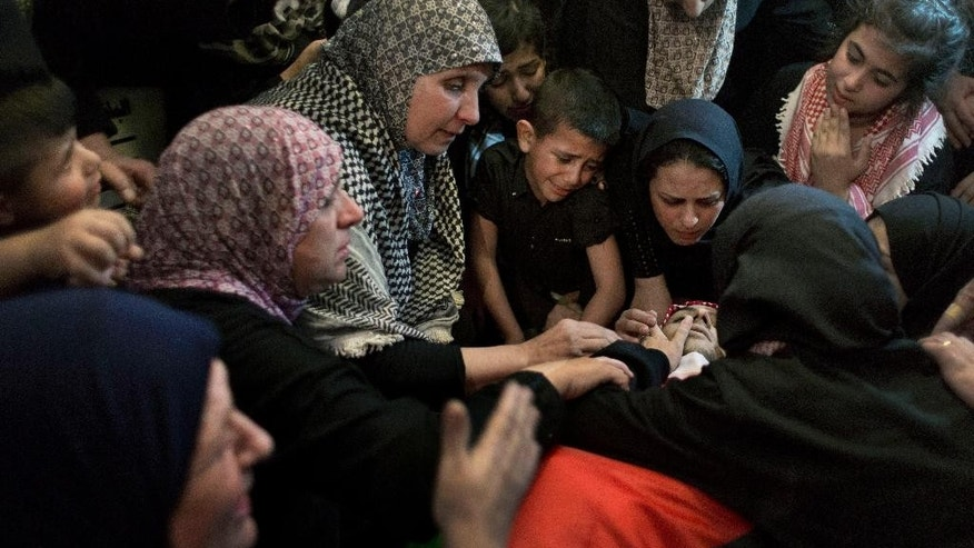 Palestinians take the last look at the body of Moataz Zawahara, who was killed in clashes with Israeli troops, during his funeral at the family house in Deheisha refugee camp, near the West Bank city of Bethlehem, Wednesday, Oct. 14, 2015. (AP Photo/Nasser Nasser)