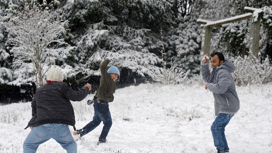 Syrian refugees play in the snow at the refugee home in the former Rehberg Hospital in the Harz mountains in St. Andreasberg, Germany, Oct. 14, 2015. (Swen Pfoertner/dpa via AP)