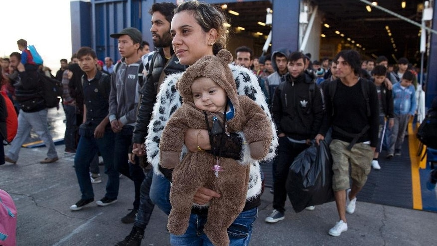 A Syrian woman carrying a baby disembarks from a ferry upon arrival from the Greek island of Lesbos at the Athens' port of Piraeus Wednesday, Oct. 14, 2015. The International Organization for Migration said more than 593,000 people have crossed this year — of which 453,000 traveled from Turkey to Greece, which has faced a massive influx of people from Syria. (AP Photo/Petros Giannakouris)