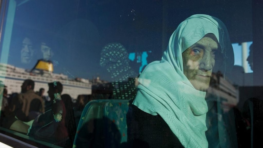 An elderly Syrian woman looks out from a window of a bus after her arrival aboard a ferry from the Greek island of Lesbos at the Athens' port of Piraeus Wednesday, Oct. 14, 2015. The International Organization for Migration said more than 593,000 people have crossed this year — of which 453,000 traveled from Turkey to Greece, which has faced a massive influx of people from Syria. (AP Photo/Petros Giannakouris)